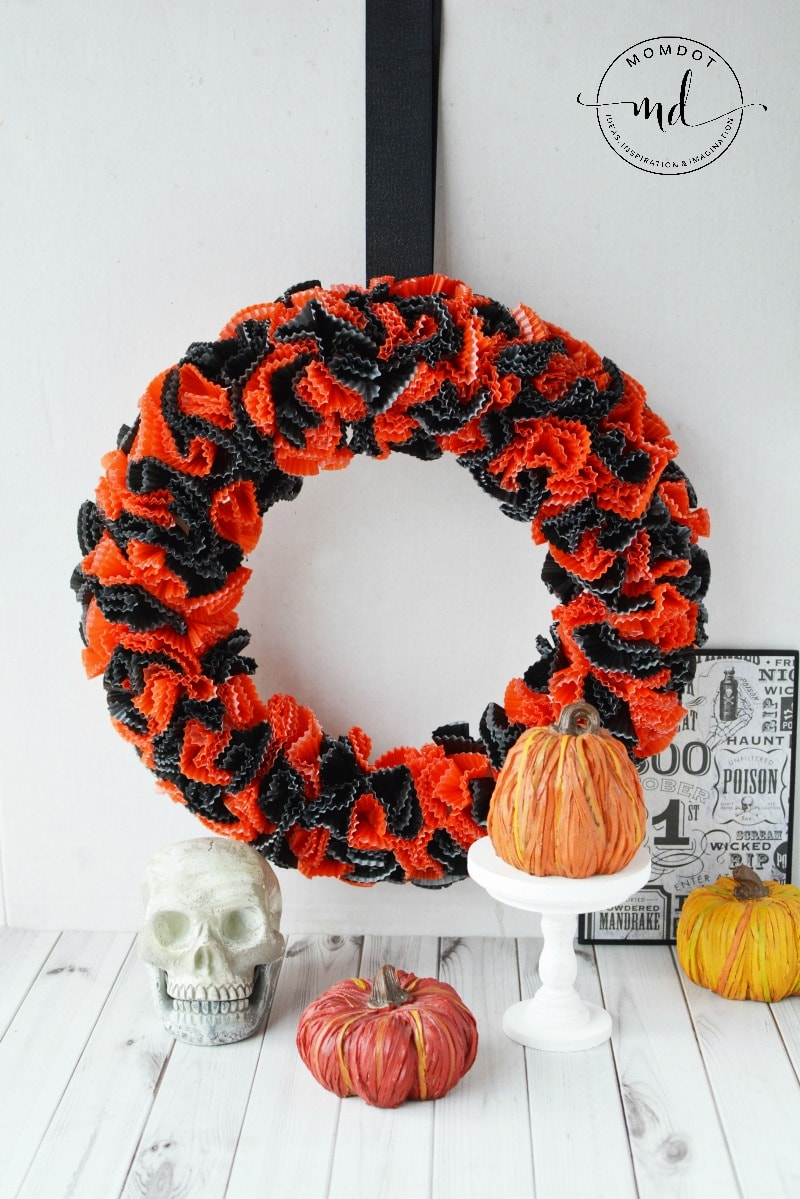 How to make a Halloween wreath with cupcake wrappers, which is perfect for mantel or hanging in your home. You will find a step by step DIY tutorial below <a href=