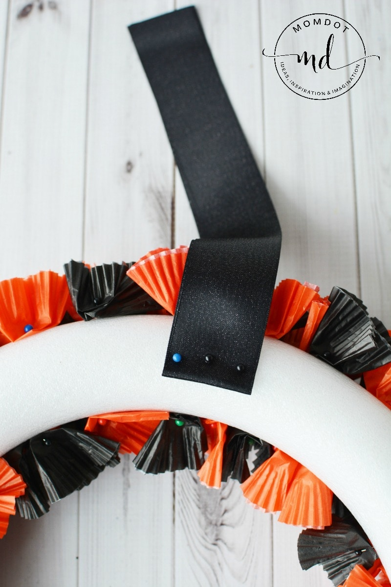 How to make a Halloween wreath with cupcake wrappers, which is perfect for mantel or hanging in your home. You will find a step by step DIY tutorial below for your cupcake wrapper wreath. Have fun!